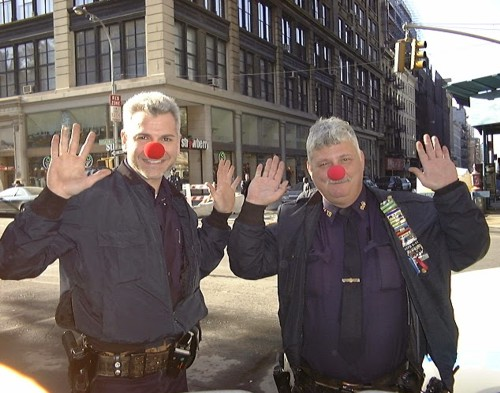 two New York police officers at Ground Zero wearing red clown nose with hands up in surrender