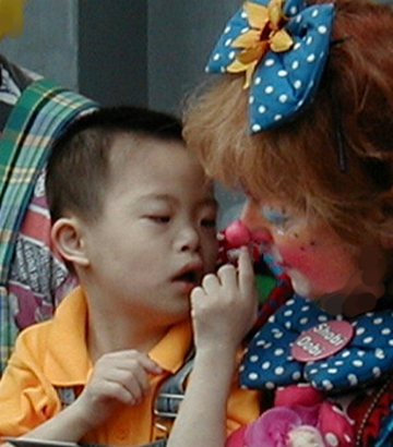 An young boy examining Clown Shobi's Clown nose